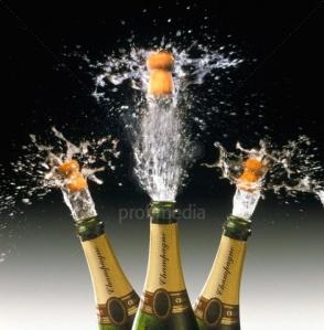 three champagne bottles pop